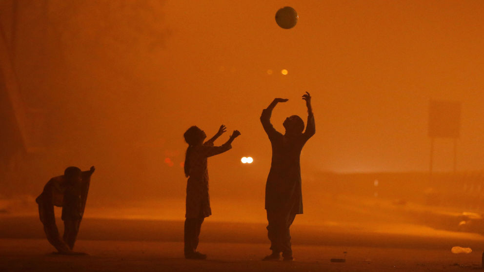 Girls play with a balloon under a flyover amidst the heavy smog in New Delhi
